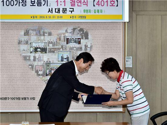 '서대문구 100가정 보듬기 사업' 수혜자에서 후원자가 된 김해자 씨(오른쪽)가 문석진 서대문구청장에게 후원약정서를 전달하고 있다.