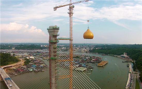 지난 20일(현지시간) 대림산업이 순가이 브루나이 대교의 주탑 꼭대기에 돔을 설치하고 있는 모습.(사진= 대림산업)