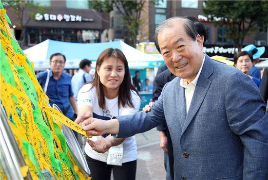 박홍섭 마포구청장(오른쪽)이 젠트리피케이션 극복과 축제의 성공 기원 메시지를 적은 리본을 매달고 있다.
