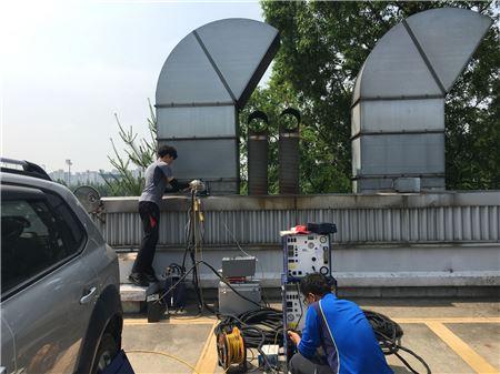 성남시 공무원이 자동차 정비업소 굴뚝에서 시료를 채취하고 있다.