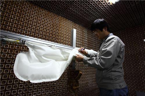 ▲코오롱인더스트리 직원이 사이드 에어백 쿠션의 품질검사를 하고 있다.