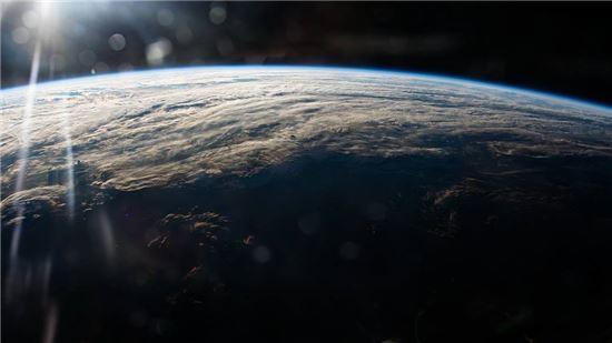 ▲햇살, 흰 구름, 둥근 지평선이 보이는 지구. 평화로워 보인다. 제프 윌리엄스가 지난 1일 촬영한 것이다.[사진제공=NASA]