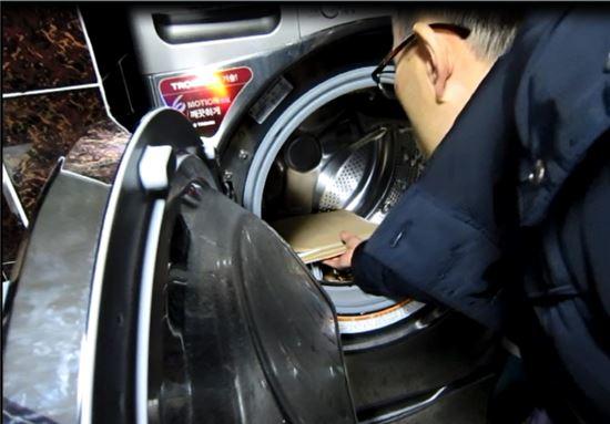 국세청 직원이 고액체납자가 세탁기에 숨긴 체권서류를 꺼내고 있다.(사진:국세청)