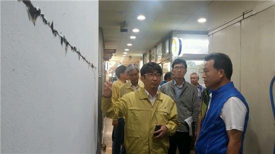김문환 대구경북지방중기청장(왼쪽)이 경주 중앙시장을 방문해 상인회장으로부터 균열 등 지진 피해 현황을 듣고 있다.