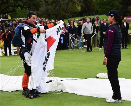 전인지가 에비앙챔피언십 우승 직후 대회 전통에 따라 스카이다이버가 건네주는 태극기를 받고 있다. 에비앙(프랑스)=LPGA