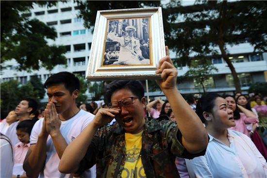 14일 태국 국민들이 전날 푸미폰 아둔야뎃 태국 국왕(88)의 영면(永眠) 소식에 국왕의 사진을 들고 거리에 나와 애도하고 있다. (사진출처=블룸버그)