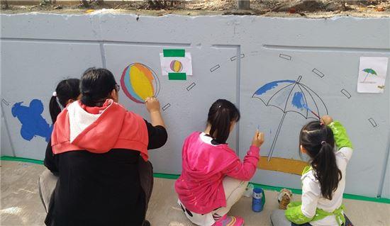 어린이들이 '그림이 있는 우리동네 마을잔치'에서 오현초등학교 담벼락에 벽화를 그리고 있는 모습