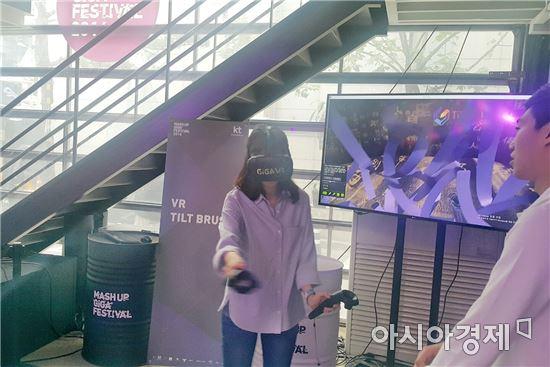 지난 22일 KT 매시업 기가 페스티벌의 관람객이 VR용 헤드업디스플레이를 쓰고 구글 틸트 브러시 프로그램으로 그림을 그리고 있다.