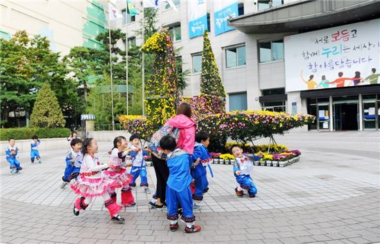 동대문구청 광장에 설치된 꽃 조형물(종이학) 앞에서 아이들이 신나게 뛰어 놀고 있다.