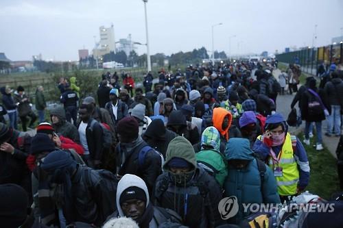 칼레 난민들이 24일 칼레 난민촌 '정글' 철거 및 분산 수용에 앞서 심사를 받기 위해 줄을 서 있다. [사진=AP·연합뉴스]