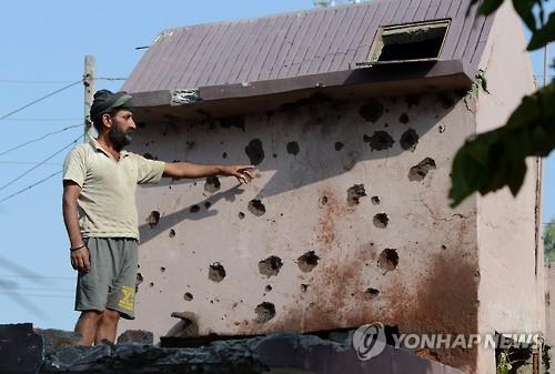24일 인도령 카슈미르 국경 지역인 카나차크에서 한 주민이 외벽에 남은 탄흔을 가리키고 있다. [사진=AFP·연합뉴스]
