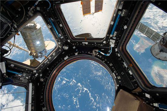 ▲국제우주정거장의 큐폴라. 왼쪽 창 바깥으로 시그너스 호가 보인다.[사진제공=NASA]