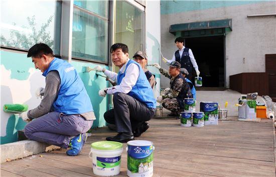 KCC와 한국미래환경협회 관계자들이 중증장애인시설 '해내기 보호작업장'에 친환경 페인트를 칠하고 있다.