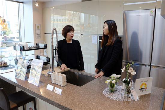 KCC 직원이 홈씨씨인테리어 전시판매장을 방문한 고객과 이야기를 나누고 있다.