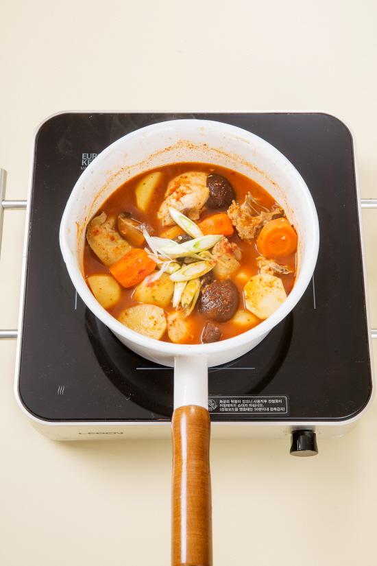4. 닭이 어느 정도 익으면 매운 양념 재료를 섞어 넣고 저으면서 한소끔 끓여 대파를 넣는다.