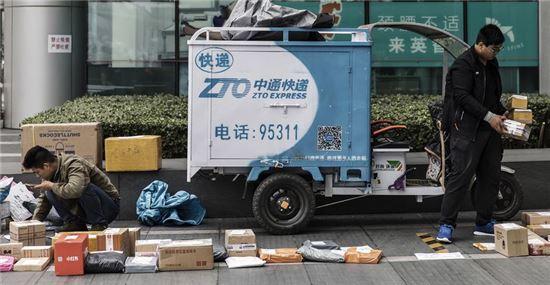 ▲ZTO 직원이 길가에 택배 물건을 늘어놓고 분류하고 있는 모습(사진=블룸버그)