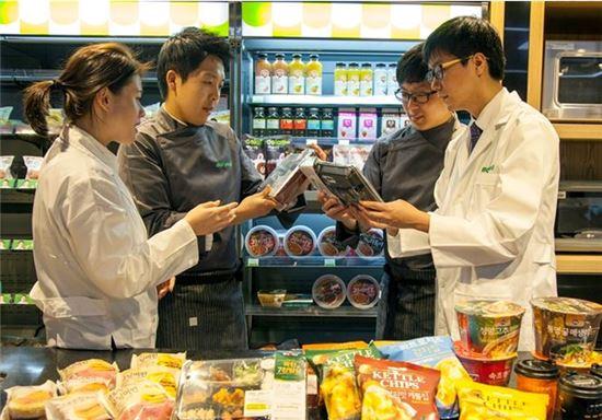 편의점 상품개발자들이 PB제품을 살펴보고 있는 모습.