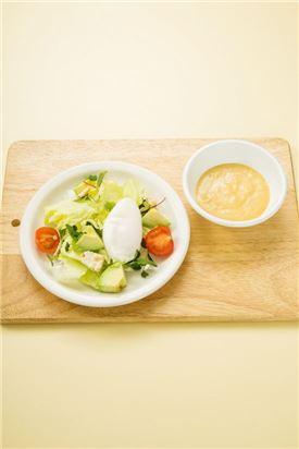 4. 그릇에 샐러드 채소를 담고 포치드 에그, 크래커, 아보카도, 토마토를 올리고 시저 드레싱을 곁들인다.