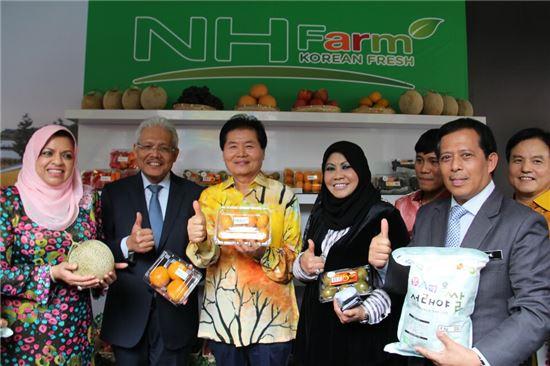 김병원 농협 회장(가운데)은 11월1일 말레이시아에서 말레이시아 정부 관계자들과 국산 농산물을 들고 기념촬영을 하고 있다.