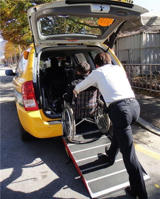 휠체어를 이용하는 시민이 기사의 도움을 받아 장애인콜택시에 오르고 있다.