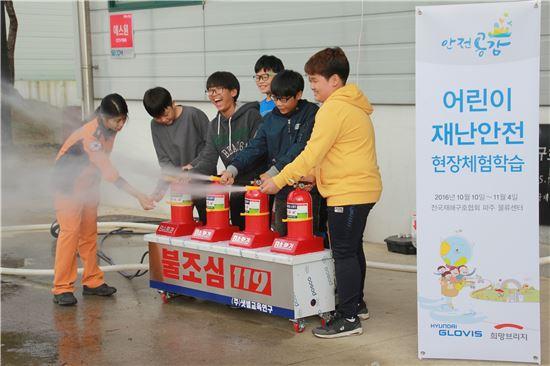 지난달 25일 어린이 재난 안전 현장 체험 행사에 참여한 서울 매봉초등학교 학생들이 소화기를 활용한 화재 진압 체험을 하고 있다. (사진 제공=현대글로비스)