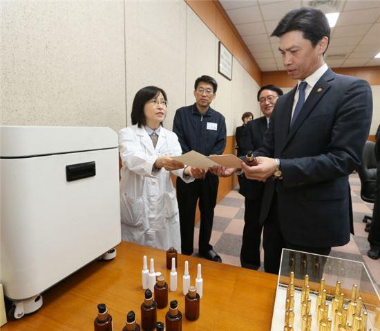 14일 오후 충북 청주시 LG생활건강 청주공장을 방문한 손문기 식품의약품안전처장(오른쪽)이 맞춤형 화장품을 살펴보고 있다.