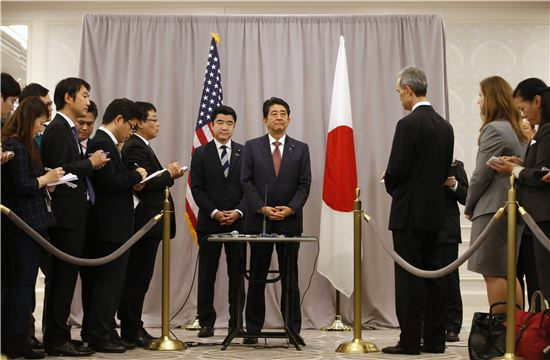 ▲도널드 트럼프 미국 대통령 당선인과의 회담을 마친 아베 신조 일본 총리(가운데)가 17일 기자회견을 열고 있다. (AP=연합뉴스)