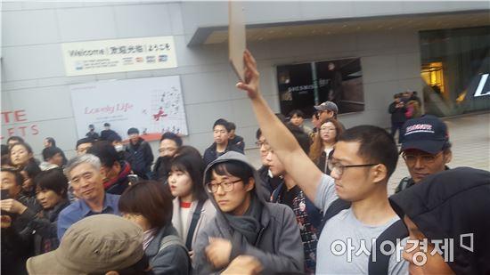 서울역 앞 하이마트에서 박근혜 퇴진 피켓을 들고 1인 시위중인 김병수 씨. 회색티셔츠를 입고 있다.