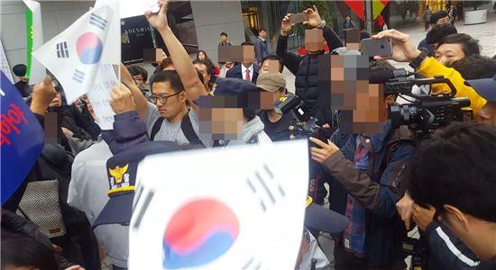 경찰이 보수집회 참가자에게 태극기로 뒤통수를 맞는 모습이다. 사진=동영상 화면 캡처.
