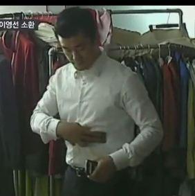 ▲이 전 행정관이 최씨에게 핸드폰을 건네기 전 자신의 셔츠에 닦고 있는 모습. (사진=SBS 방송 캡쳐)