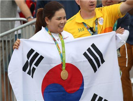 박인비가 리우올림픽에서 금메달을 따낸 뒤 태극기를 펼쳐 들고 환하게 웃는 모습.