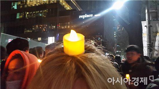 ▲ 26일 광화문 집회에서는 이색 양초를 든 시민들의 모습이 눈에 띄었다. 양초 머리띠를 끼고 온 시민의 모습.