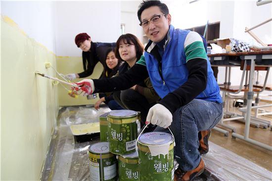 자원봉사자들이 해오름 지역아동센터에서 친환경 페인트로 작업을 하고 있다.