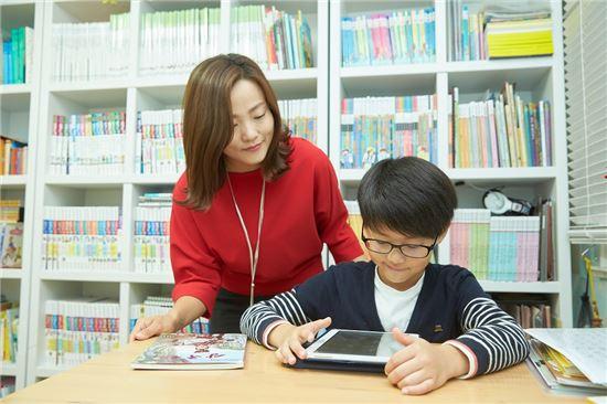 초등학생 어린이가 웅진북클럽을 이용해 독서를 하고 있다.