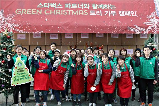스타벅스커피 코리아 임직원들이 초록우산 어린이재단과 함께 전국의 지역사회 아동 기관에 크리스마스 트리 700여개를 기부하는 봉사활동을 전개하고, 기념사진을 찍고 있다.
