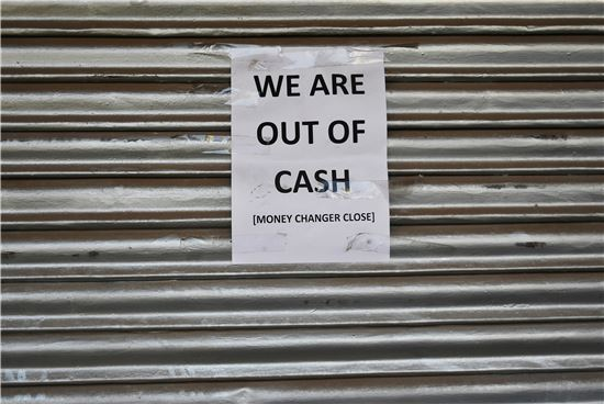 인도 뉴델리 소재 한 신권 교환소의 셔터가 굳게 닫힌 가운데 '신권이 모두 떨어졌다'는 안내문만 붙어 있다(사진=블룸버그뉴스).
