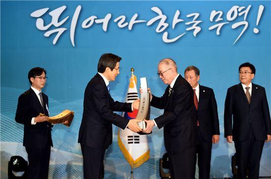 박준 농심 대표이사가 황교안 국무총리로부터 1억불 수출의 탑 트로피를 받고 있다.
