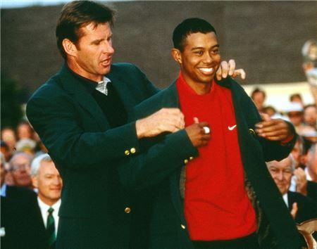 타이거 우즈는 마스터스 통산 평균타수 1위다. 닉 팔도(왼쪽)가 1997년 우즈에게 그린재킷을 입혀주고 있는 모습.