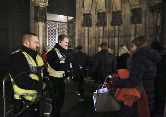 ▲크리스마스 이브 미사에 참석하기 위해 들어가는 사람들의 짐을 검사하고 있는 경찰관. (EPA=연합뉴스)