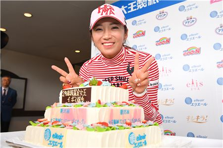 이보미가 2년 연속 일본의 상금퀸에 오른 뒤 축하 케이크 앞에서 미소를 짓고 있다.
