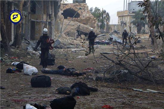 ▲시리아 '하얀 헬멧' 민방위대들이 폭격으로 인해 참혹하게 부서진 거리에 서 있다. (AP=연합뉴스)