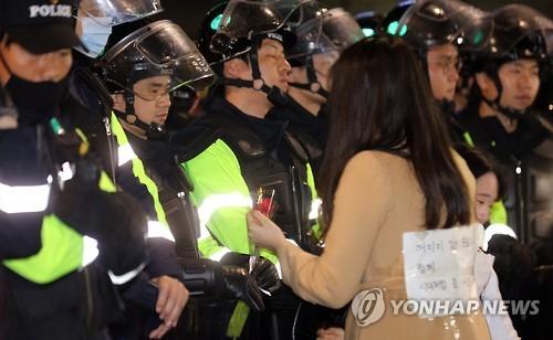 지난달 19일 오후 청와대 진입로인 종로구 내자동 로터리에서 박근혜 대통령 퇴진촉구 촛불집회에 참가한 한 여성이 시위대를 막고 있는 경찰에게 장미꽃을 건네고 있다. (사진=연합뉴스)