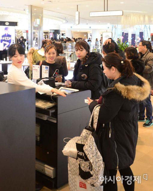롯데면세점 월드타워점에서 중국인 고객들이 줄을 서서 화장품을 구매하고 있다.