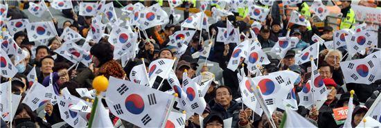 6일 서울 용산구 전쟁기념관 앞에서 열린 탄핵반대 집회에서 참석한 시민단체 회원들이 태극기를 흔들고 있다. / 사진=연합뉴스