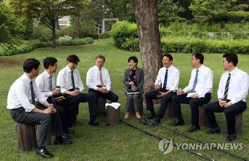 문재인 대통령이 11일 청와대 참모들과 함께 점심 식사를 한 뒤 손에 커피를 들고 청와대 경내에서 이야기를 나누고 있다. 사진/연합뉴스