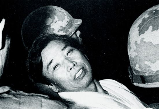 1979년 12월 육군본부 계엄보통군법회의 재판정에서 피고인석으로 다가오는 가족에게 환한 표정을 지어보이는 김재규. '<격동의80년대>자료사진.