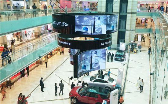 LG전자가 인도 구르가온에 위치한 쇼핑몰인 엠비언스몰(Ambience Mall)에 설치한 대형 올레드 사이니지. 55인치 플렉서블 올레드 사이니지 70장을 활용해 가로 6미터, 높이 5.7미터 크기의 웅장하고 심미적인 사이니지 조형물을 완성했다.