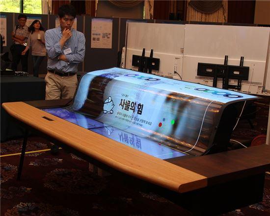 LG디스플레이가 세계 최초 개발한 77인치 투명 플렉시블 디스플레이가 적용되어 용도에 맞게 접었다 폈다 변형 가능한 스마트 데스크 제품을 참관자가 살펴보고 있다.(현 기사와는 무관)