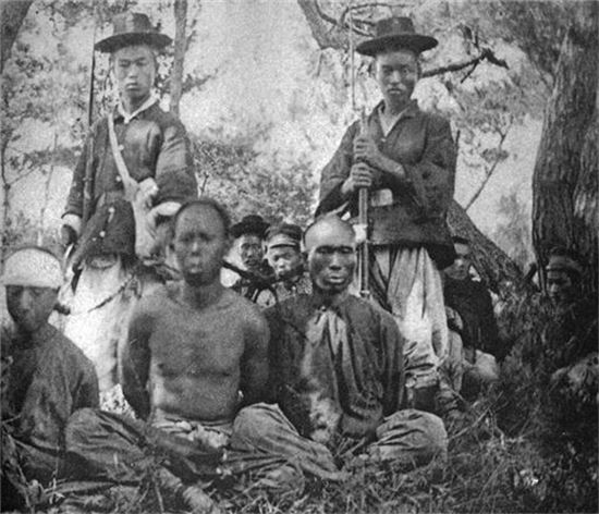 청일전쟁 당시 보초를 서고 있는 조선군과 청군포로들 모습. 사진 뒤쪽에 조선인들과 일본군 모습도 보인다. 청군 포로 중에는 조선 지방군들도 섞여있었다.(사진=위키피디아)