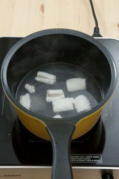 2. 오징어는 내장을 떼어내고 껍질을 벗긴 후 잔 칼집을 내어 한입 크기로 썰어 끓는 물에 데친다.